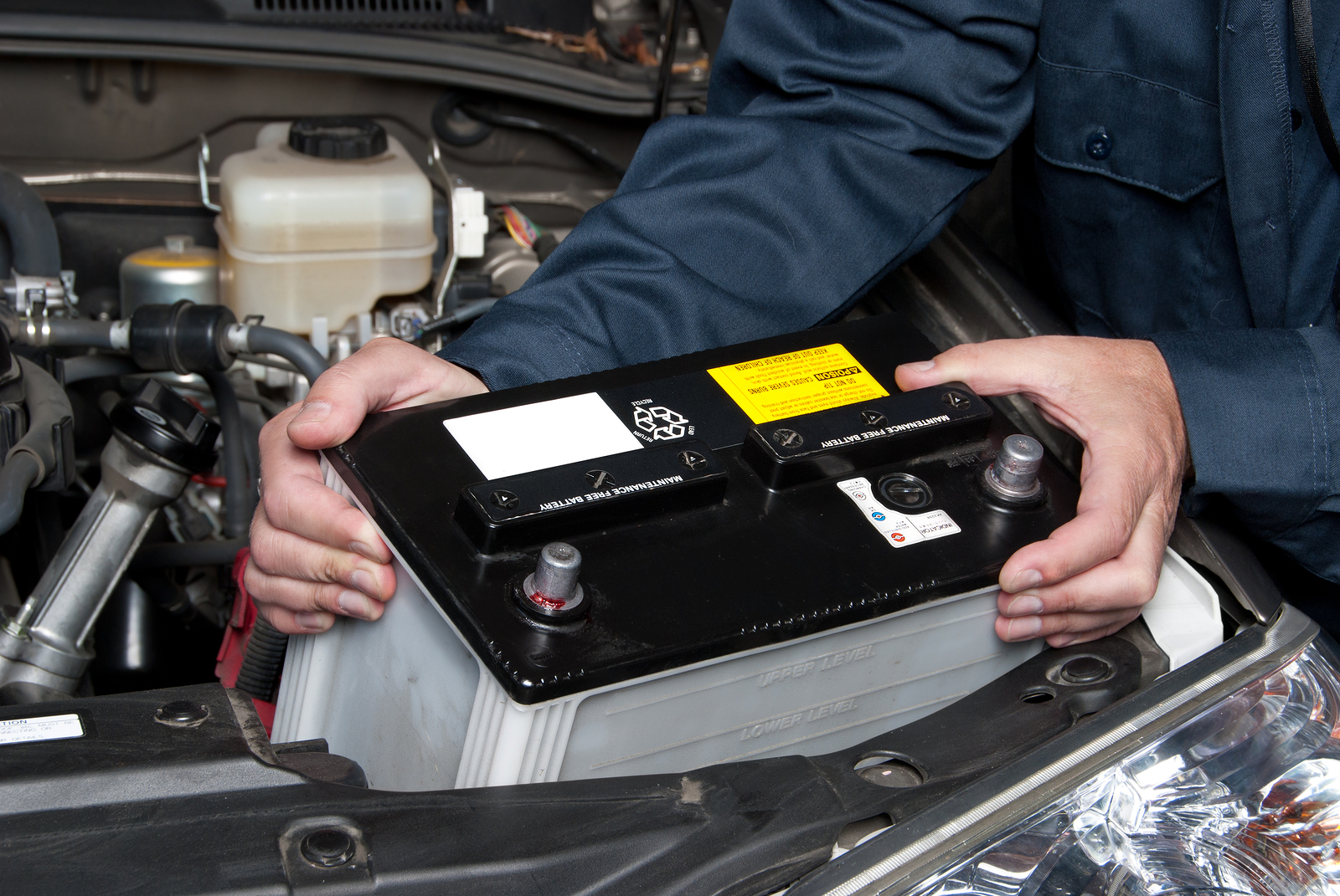 two hands holding a car battery
